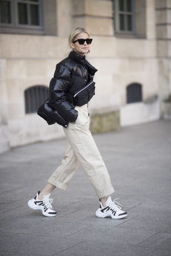 a cool look with neutral pants, a puffy black jacket, a black bag and black and white trainers