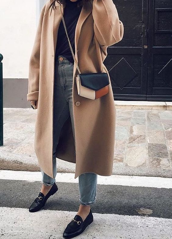 a black turtleneck, bleached cropped jeans, black loafers, a camel coat and a color block bag