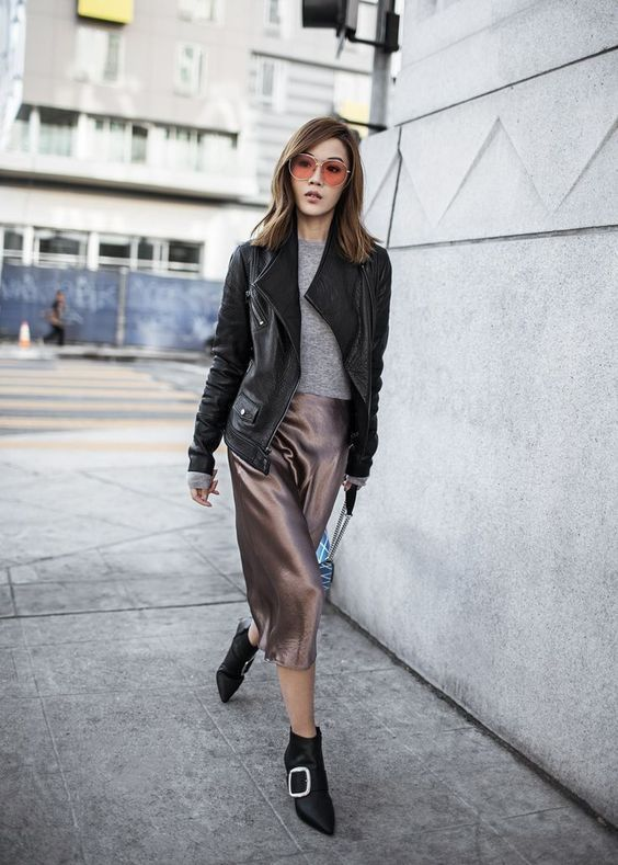 a grey sweater, a taupe silk midi skirt, black boots and an oversized leather jacket