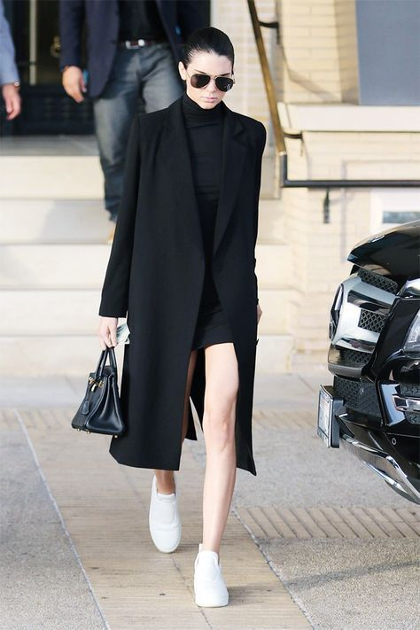 a black straight coat, a black turtleneck dress, white snakers worn by Kendall Jenner for a minimalist chic outfit