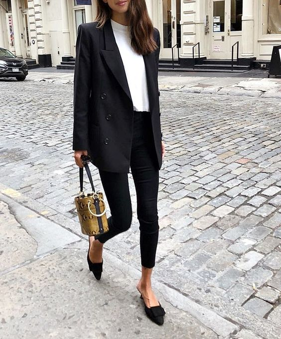 a chic look with a black oversized blazer, black skinnies, a white turtleneck, black mules and a bucket bag