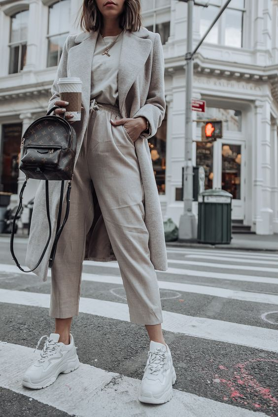a layered neutral outfit with pants, a tree, a coat, white sneakers and a small black backpack