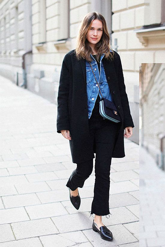 black jeans with a raw hem, black loafers, a blakc tee, a blue denim jacket, a black coat and a black bag