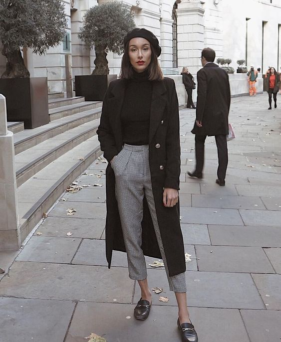 a classic and minimalist outfit with a black turtleneck, printed pants, blakc loafers, a black coat and a beret