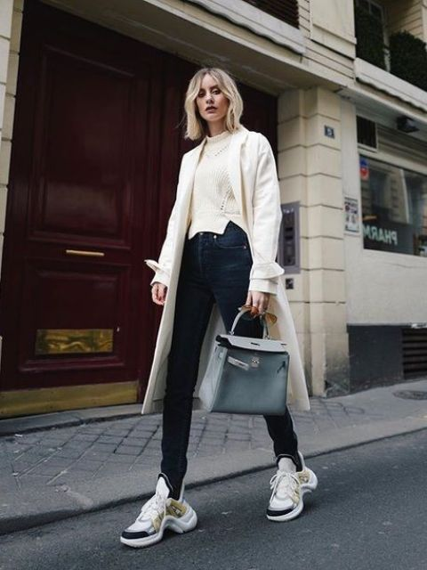 a neutral sweater, black jeans, a white trench, white and black trainers and a powder blue bag