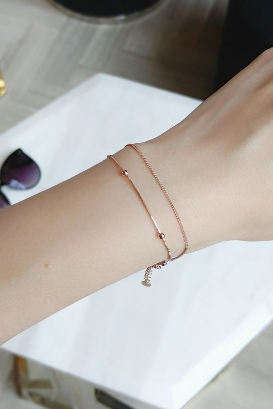 a rose gold chain bracelet with tiny beads  and a little coin is a stylish minimalist idea
