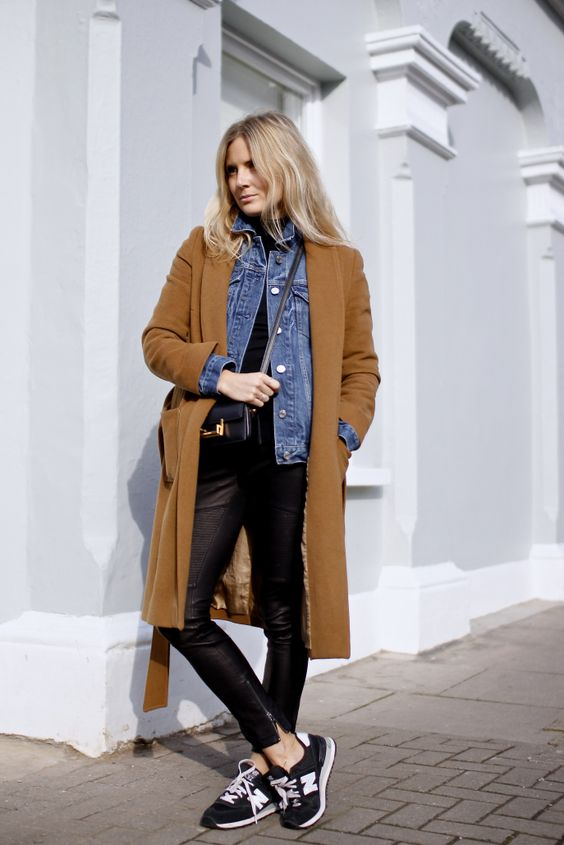 black leather pants, black trainers, a black top, a blue denim jacket, a camel coat and a black crossbody