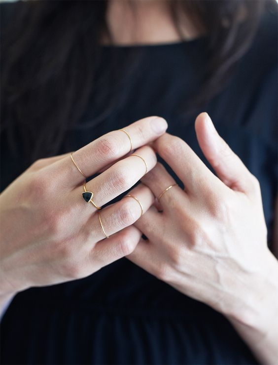minimalist gold rings and a single black triangle one for a contrasting touch