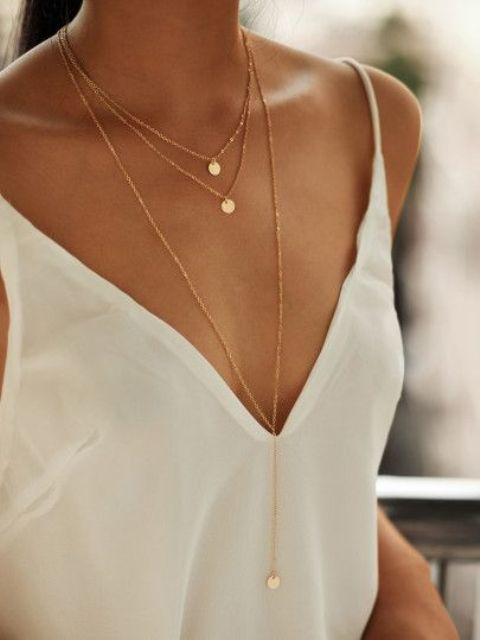 a layered gold necklace with little coins and a longer pendant is a stylish minimal idea
