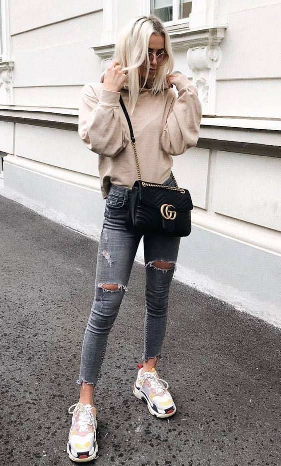 a neutral sweatshirt, grey ripped jeans, neutral trainers with colorful splashes and a black bag