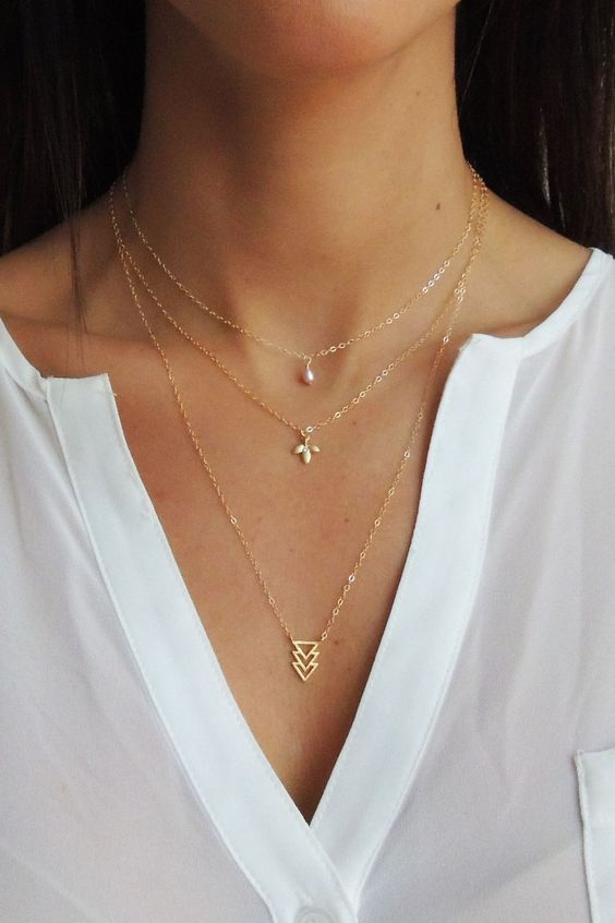 a trio of minimalist necklaces with a triangle, a leaf and a single pearl is a minimal and boho idea