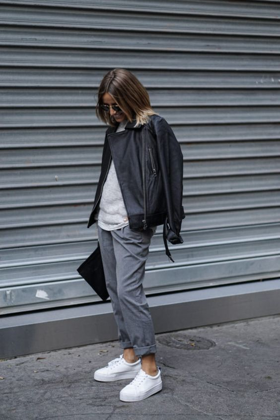 a minimalist look with grey pants, a grey top, white sneakers and a black leather jacket plus a clutch