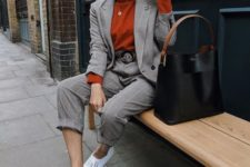 11 a printed pantsuit with an oversized blazer, white sneakers, a rust-colored turtleneck and a black bag