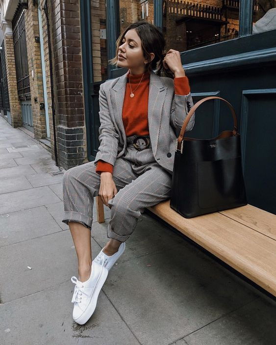a printed pantsuit with an oversized blazer, white sneakers, a rust-colored turtleneck and a black bag
