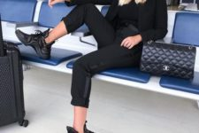 11 a total black look with a pantsuit, a black turtleneck, trainers, a bag is nice for travelling, too