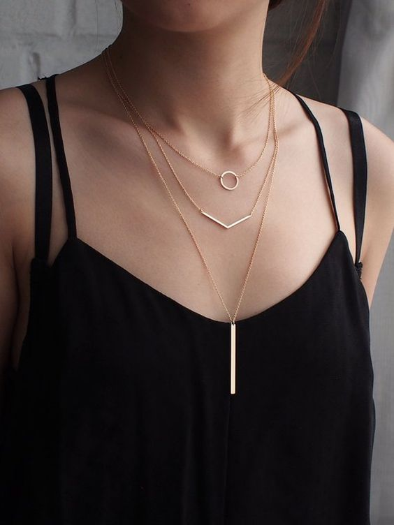 geometric layering necklaces with a circle, a geometric line and a long wide bar hanging down