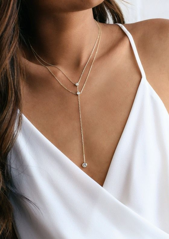 layered gold and diamond necklaces with contrasting lengths are a stylsh minimalist idea