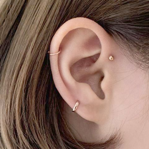 a single gold stud and a duo of gold hoops of various width for minimalist styling