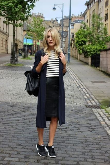 a striped top, a black leather skirt, black trainers, a navy cardigan and a black backpack