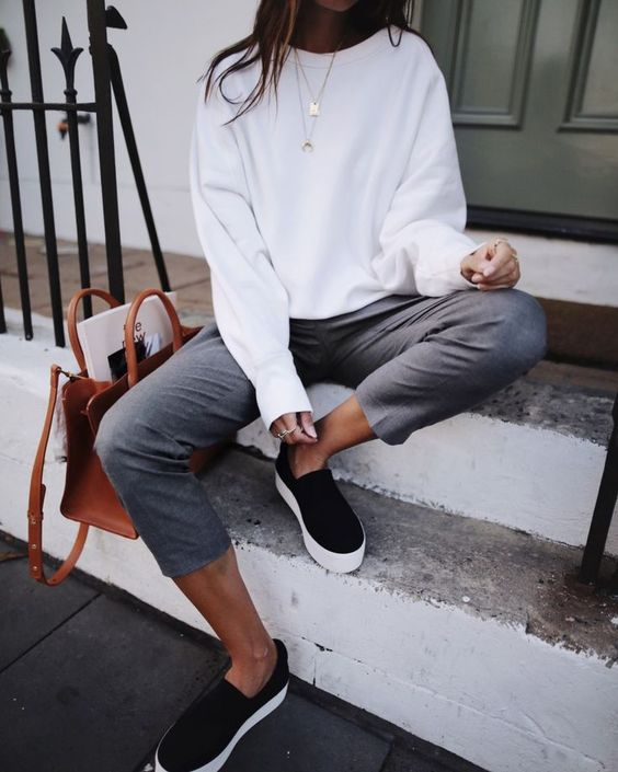 a white sweatshirt, grey cropped pants, black slipons, layered necklaces and a brown bag