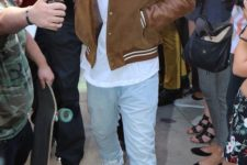 Drake wearing a white t-shirt, bleached jeans, white trainers and a brown leather bomber jacket