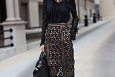 With black blouse, black bag and pumps