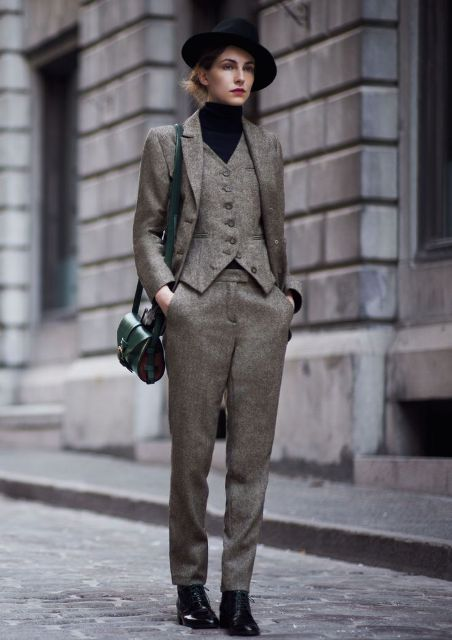With black hat, black turtleneck, emerald bag and black lace up boots