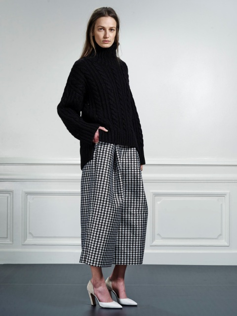With black oversized sweater and white pumps