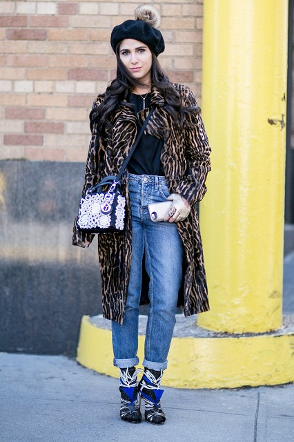With black shirt, cuffed jeans, unique boots, white and navy blue bag and animal printed coat