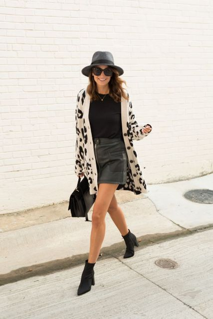 With black shirt, gray wide birm hat, leather skirt, black ankle boots and bag