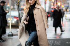 With black turtleneck, beige midi coat, jeans and beige clutch