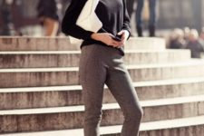 With black turtleneck, white clutch and gray skinny trousers