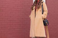 With cap, beige midi coat, black bag and black high heeled boots