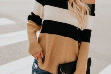 With distressed jeans and black clutch