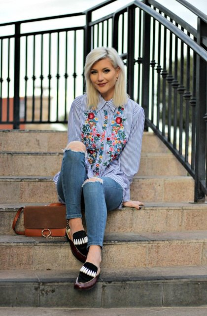 With floral blouse, distressed jeans and brown bag