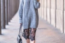With gray long sweater, black boots and bag