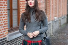 With gray turtleneck, red beret and black leather bag