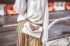 With light gray oversized sweater and embellished crossbody bag