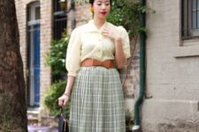 With light yellow blouse, brown leather bow belt, white and black flat shoes and black bag