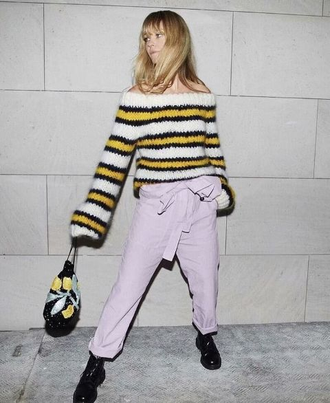With lilac belted trousers, printed bag and black flat boots