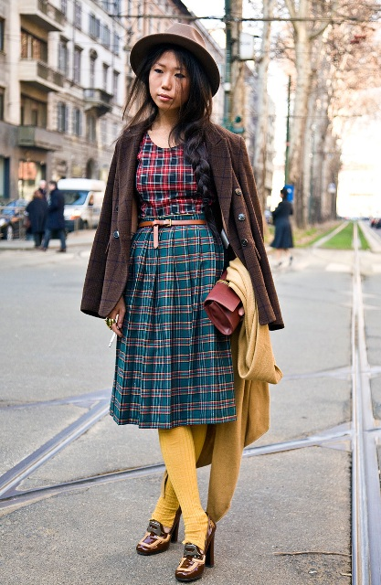 With plaid shirt, hat, brown jacket, clutch, yellow tights and heeled shoes
