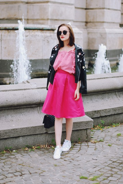 With striped blouse, pink A-line skirt, white sneakers and black bag