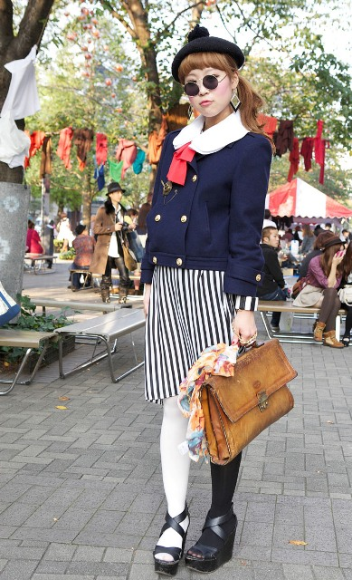 With striped skirt, navy blue jacket, brown leather bag and platform shoes