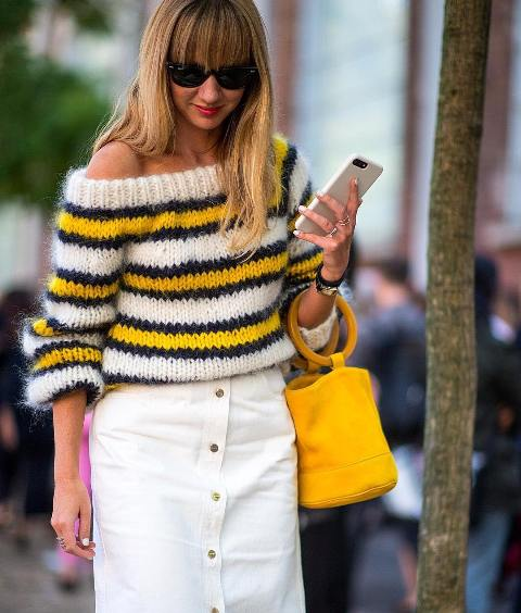 With white high-waisted skirt and yellow bag