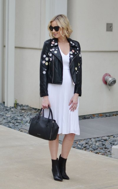 With white knee length dress, black bag and black ankle boots