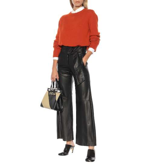 With white shirt, orange sweater, two colored bag and black mules