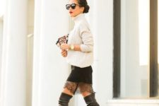 With white sweater, printed bag and black leather over the knee boots