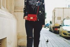 With wide brim hat, labeled t-shirt, red bag, distressed pants and flat shoes