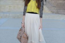 With yellow shirt, beige midi skirt, bag and silver sandals