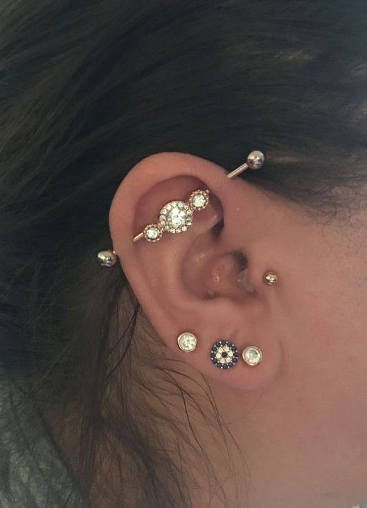 a beautifully accessorized ear with three lobe piercings, a tragus and an industrial one all done with similar studs and a bar